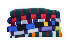 Stapel multicolored gestreepte die de winterkleren op witte achtergrond worden geïsoleerd stock foto