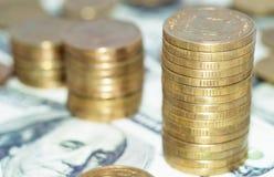 Stapel muntstukken op dollars Royalty-vrije Stock Foto's