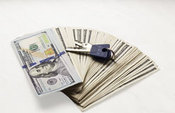Stapel nieuwe honderd-dollar bankbiljetten met sleutels op witte achtergrond Het verdienen van inkomensgeld van onroerende goeder Stock Foto