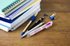 Stapel notebads en pennen op houten lijst stock afbeeldingen