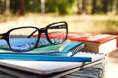 Stapel Notizbücher mit Gläsern und Buch auf Bank Stockfoto