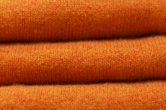 Stapel orange woolen Strickjacken Nahaufnahme, Beschaffenheit, Hintergrund Tendenz groben Tuchs stockfotos
