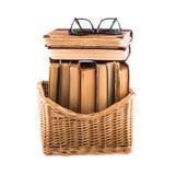 Stapel oude antieke boeken in een rieten mand en bril die op bovenkant liggen Stock Afbeeldingen