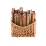 Stapel oude boeken in een rieten mand en bril in dik-omrand Stock Afbeeldingen