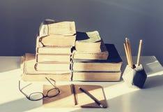 Stapel oude boeken, handboek, glazen en potloden op bureauachtergrond voor onderwijs retro concept stock afbeeldingen