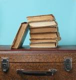 Stapel oude boeken op retro koffer op een blauwe achtergrond royalty-vrije stock foto
