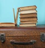 Stapel oude boeken op retro koffer op een blauwe achtergrond stock afbeeldingen
