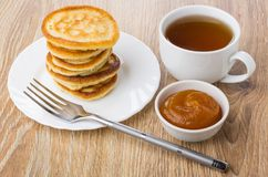 Stapel pannekoeken in plaat, vork, kom met abrikozenjam Royalty-vrije Stock Foto's