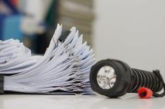 Stapel Papierarchive mit Clipn auf Schreibtisch für Bericht und Taschenlampe im Büro am Abend lizenzfreie stockbilder