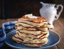 Stapel Pfannkuchen mit butteron hölzernem Hintergrund stockfotos