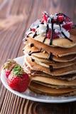 Stapel Pfannkuchen mit Erdbeeren, Peitschencreme und Schokoladensirup auf einer weißen Platte auf einem hölzernen Hintergrund Lizenzfreie Stockfotos