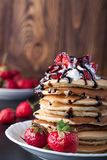 Stapel Pfannkuchen mit Erdbeeren, Peitschencreme und Schokoladensirup auf einer weißen Platte auf einem hölzernen Hintergrund Lizenzfreies Stockbild