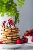 Stapel Pfannkuchen mit Erdbeeren, Peitschencreme und Schokoladensirup auf einer weißen Platte auf einem weißen Hintergrund Lizenzfreie Stockfotografie