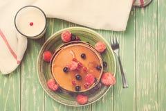 Stapel Pfannkuchen mit gefrorenen Beeren und Honig auf Holztisch Beschneidungspfad eingeschlossen getont Stockfoto