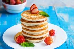 Stapel Pfannkuchenstückchen mit Erdbeeren und Honig auf einem pl stockbilder