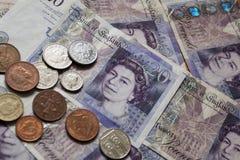 Stapel Pfund-Münzen auf zwanzig Pfund-Anmerkungen Stockbild