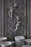 Stapel Platten auf dem Schaukasten mit Engeln auf dem Hintergrund Restaurantgeräte Flacher Fokus Lizenzfreies Stockbild