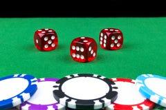 Stapel Pokerchips auf einer grünen Spielpokertabelle mit Pokerwürfeln am Kasino Spielen eines Spiels mit Würfeln Kasinowürfelkonz Lizenzfreie Stockfotos