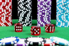 Stapel Pokerchips auf einer grünen Spielpokertabelle mit Pokerwürfeln am Kasino Spielen eines Spiels mit Würfeln Kasinowürfelkonz Stockfotos