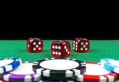 Stapel Pokerchips auf einer grünen Spielpokertabelle mit Pokerwürfeln am Kasino Spielen eines Spiels mit Würfeln Kasinowürfelkonz Lizenzfreie Stockbilder