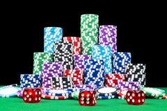 Stapel Pokerchips auf einer grünen Spielpokertabelle mit Pokerwürfeln am Kasino Spielen eines Spiels mit Würfeln Kasinowürfel Lizenzfreie Stockfotografie