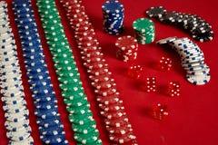 Stapel Pokerchips auf rotem Hintergrund am Kasino lizenzfreies stockbild
