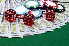 Stapel Pokerchips mit Würfeln rollt auf Dollarscheinen, Geld Pokertabelle am Kasino Pokerspielkonzept Spielen eines Spiels Stockfoto