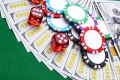 Stapel Pokerchips mit Würfeln rollt auf Dollarscheinen, Geld Pokertabelle am Kasino Pokerspielkonzept Spielen eines Spiels Lizenzfreie Stockfotografie