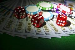 Stapel Pokerchips mit Würfeln rollt auf Dollarscheinen, Geld Pokertabelle am Kasino Pokerspielkonzept Spielen eines Spiels Lizenzfreies Stockfoto