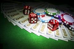Stapel Pokerchips mit Würfeln rollt auf Dollarscheinen, Geld Pokertabelle am Kasino Pokerspielkonzept Spielen eines Spiels Lizenzfreie Stockfotos
