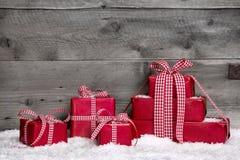 Stapel rode Kerstmisgiften, sneeuw op grijze houten achtergrond. Royalty-vrije Stock Foto