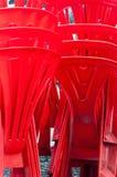 Stapel rode plastic stoelen stock afbeeldingen