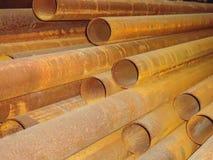 Stapel roestige staalpijpen in een industrieel pakhuis stock afbeelding
