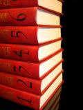 Stapel rote Bücher mit Zahlen auf schwarzem Hintergrund Stockfotos