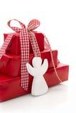 Stapel rote Weihnachtsgeschenke mit weißem Engel lokalisiert auf whi Stockfotografie