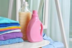 Stapel saubere Kleidung und Flaschen mit Reinigungsmittel stockfoto