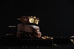 Stapel Schokolade tauchte Eis am Stiel mit abgebrochenen Nüssen auf dunklem hölzernem Brett über schwarzem Hintergrund ein Stockfotografie