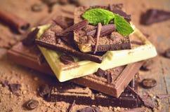 Stapel Schokoladenscheiben mit Kakaopulver Stockbilder