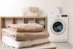 Stapel schone zachte handdoeken op mand in wasserijruimte stock foto's