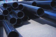 Stapel schwarze Kunststoffrohre für Wasserversorgung oder Kanalisation bereitete sich für Installation oder Reparatur des Wasserv Lizenzfreie Stockfotos