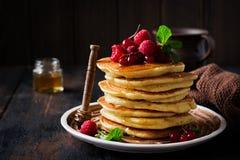 Stapel selbst gemachte kleine Pfannkuchen mit Honig, frischen Himbeeren und roten Johannisbeeren auf einem alten hölzernen Hinter stockfoto