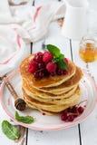 Stapel selbst gemachte kleine Pfannkuchen mit Honig, frischen Himbeeren und roten Johannisbeeren auf einem alten hellen h?lzernen stockfoto