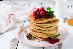 Stapel selbst gemachte kleine Pfannkuchen mit Honig, frischen Himbeeren und roten Johannisbeeren auf einem alten hellen h?lzernen lizenzfreie stockfotografie