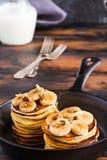 Stapel selbst gemachte Pfannkuchen mit Banane, Ahornsirup und Walnüssen in der schwarzen Roheisenbratpfanne Lizenzfreies Stockbild