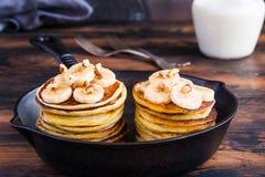 Stapel selbst gemachte Pfannkuchen mit Banane, Ahornsirup und Walnüssen in der schwarzen Roheisenbratpfanne Stockbild
