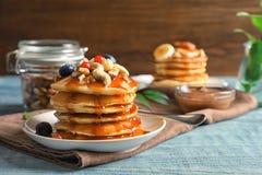 Stapel smakelijke pannekoeken met bessen, noten en stroop stock foto