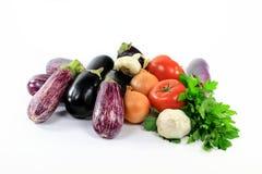 Stapel sortierte Auberginen und Gemüse auf Weiß. Lizenzfreies Stockbild