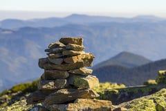 Stapel Steine bedeckt mit Moos auf einen Berg auf Gebirgshintergrund Konzept der Balance und der Harmonie Stapel Zenfelsen Lizenzfreies Stockfoto