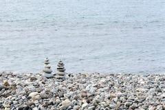 Stapel Steine in der perfekten Balance auf einem ruhigen Pebble Beach Stockfoto