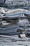 Stapel unterschiedliche alte getragene Blue Jeans Stockbilder